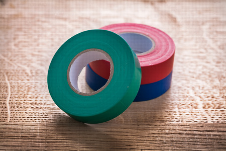cordon tape: green red blue rolls of insulating tape on wooden board construc