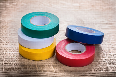 green white yellow red blue rolls of insulating tape on wooden b photo