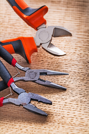 nippers: nippers and pliers on wooden board construction concept Stock Photo