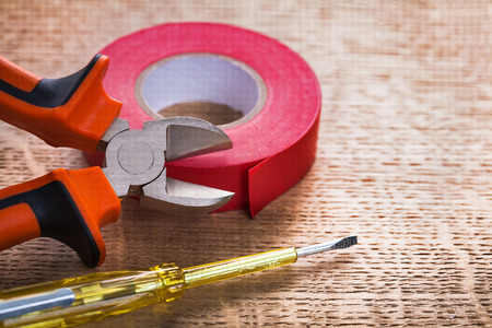 cordon tape: nippers tester roll of red insulating tape on wooden board const