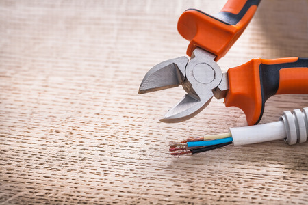 nippers: opened nippers and electrical cable on wooden board construction Stock Photo