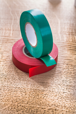 cordon tape: Red and green rolls of insulating tape on wooden board construct
