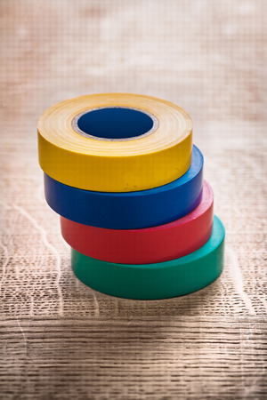 cordon tape: stack of four rolls insulating tape on wooden board construction
