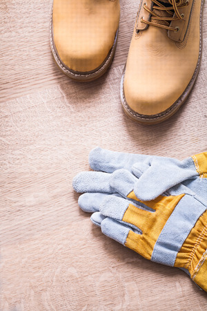 working boots and protective gloves on wooden board construction photo