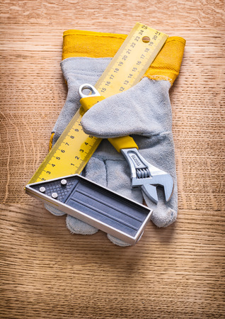 protective work wear: adjustable wrench square ruller and protective working glove on Stock Photo