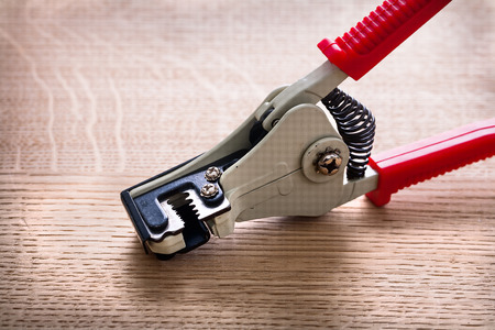 strippers: automatic wire strippers very close up on wooden board Stock Photo
