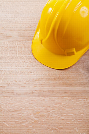 construction concept: close up view yellow helmet on wooden board construction concept