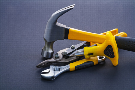 close up  wrench: hand screwdriver steel cutter claw hammer with yellow handles on
