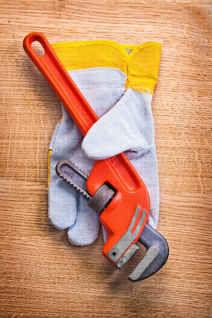 close up  wrench: monkey wrench protective work glove on wooden board construction Stock Photo