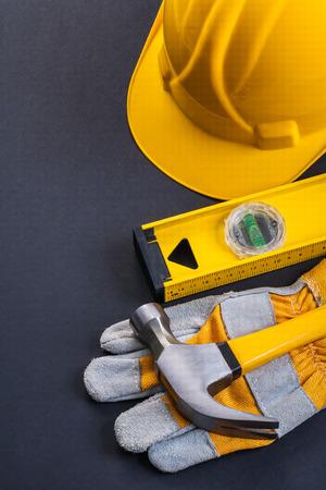 work glove: claw hammer protective work glove level helmet on black backgrou Stock Photo