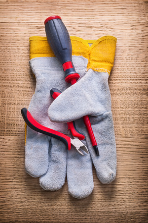 wirecutters: little nippers screwdriver and protective working glove on woode Stock Photo