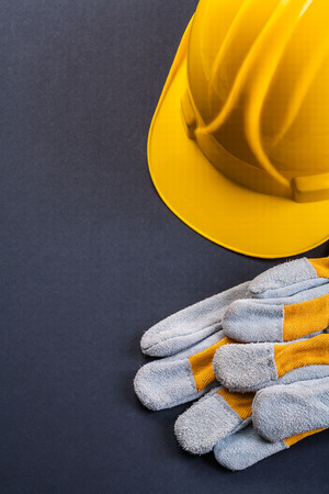 work gloves: pair of protective work gloves and yellow helmet on black backgr