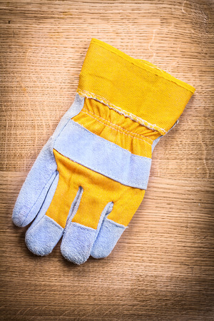 protective work wear: protective work glove on wooden board construction concept
