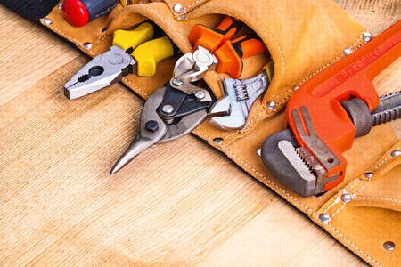 close up  wrench: toolbelt with tools on wooden board
