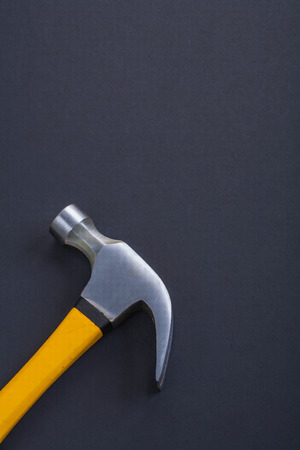 claw hammer: vertical version claw hammer with yellow handle on black backgro