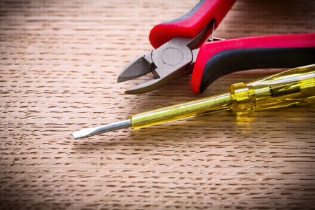 wirecutters: very close up electrical tester and nippers on wooden board