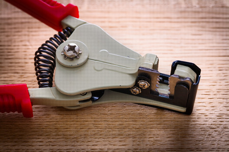 wirecutters: very close up view automatic wire strippers on wooden board
