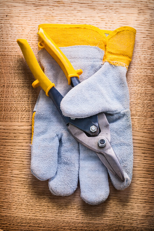 wirecutters: stell cutter with yellow handles and protective working glove on wooden board construction concept Stock Photo
