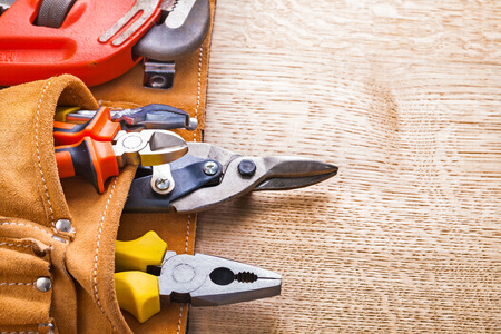 wirecutters: set of tools in tollbelt pliers cutter nippers wrench on wooden board