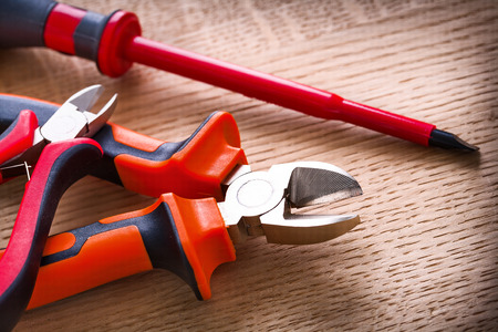 wirecutters: red electric insulated screwdriver and two nippers on wooden board Stock Photo