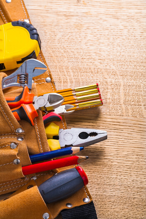 wirecutters: tools in belttape measure wrench nippers pliers pencil on wooden board Stock Photo