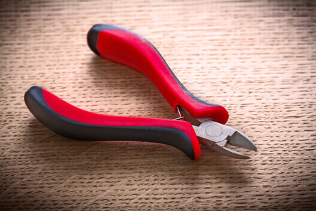 wirecutters: small nippers with black red handles on wooden board