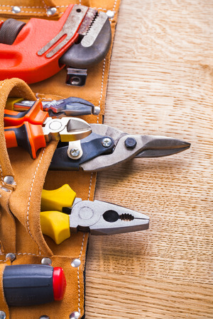 toolbelt: vertical view monkey wrench nippers steel cutter pliers screwdriver in toolbelt on wooden board Stock Photo