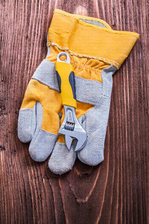 adjustable: Adjustable spanner and protective glove on wood board