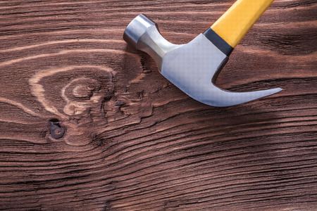 claw hammer: Metal claw hammer on brown vintage wooden board Stock Photo