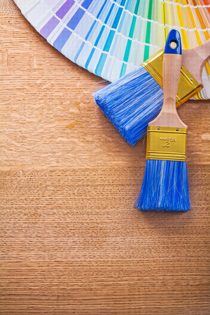multi colored: Multi colored color palette and paint brushes on wooden board Stock Photo