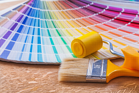 paint swatch: Paint roller, brush and color palette guide on wooden board Stock Photo