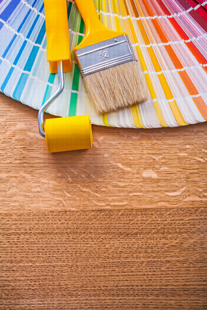 roller brush: Paint roller, brush and color palette on wooden board Stock Photo
