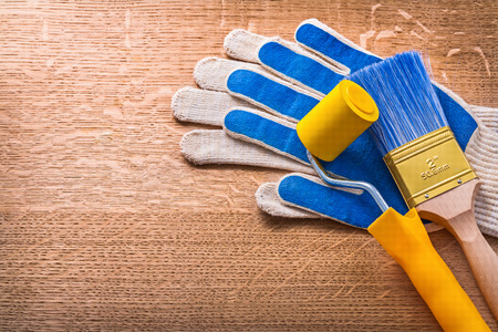 roller brush: Paint roller, brush and protective gloves on wooden board