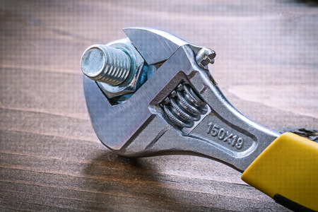 threaded: Vintage wooden board with adjustable spanner and metal threaded bolt Stock Photo