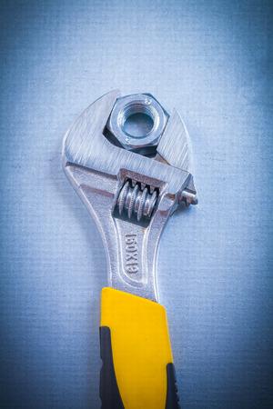 screw key: Adjustable key and stainless screw nut on metallic background co