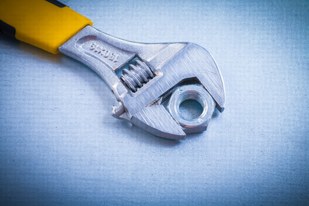 threaded: Adjustable spanner and threaded screw nut on metallic background
