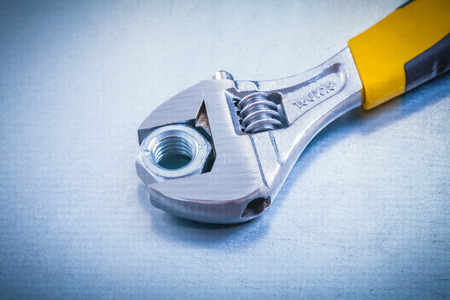adjustable spanner: Adjustable spanner and screw nut on metallic background construc Stock Photo
