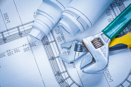 adjustable: Adjustable spanners and blueprint rolls construction concept Stock Photo