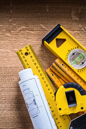 Blueprints and collection instruments of measurement on oak wood board construction concept photo