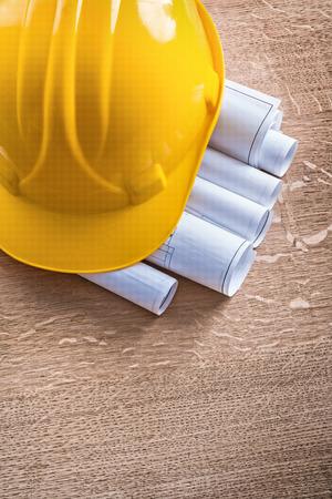 oaken: Building helmet and blueprint rolls on wooden oaken board constr