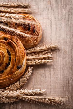 oaken: Bunches of golden wheat ears pastry with raisins on oaken wooden