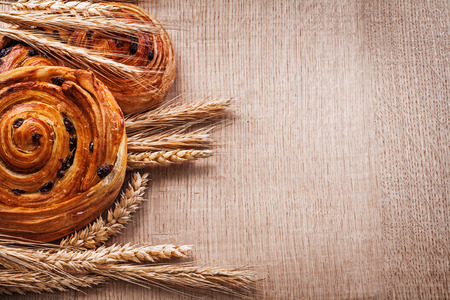 oaken: Bunches of golden wheat ears rolls with raisins on oaken wooden