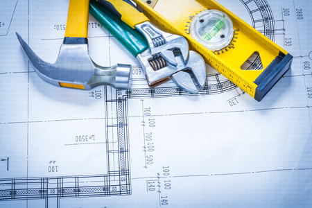 building maintenance: Claw hammer adjustable spanners construction level on blueprint