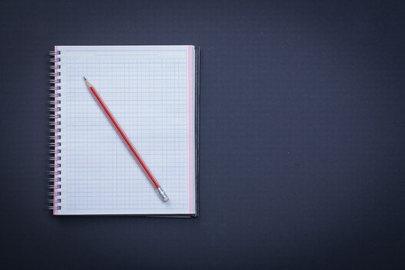 workbook: Clean squared workbook with red pencil on black background educa Stock Photo