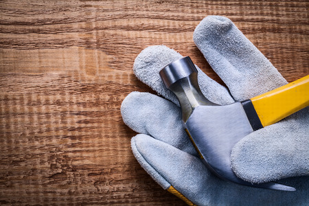 to woo: close up view claw hammer in protective glowe and on vintage woo Stock Photo