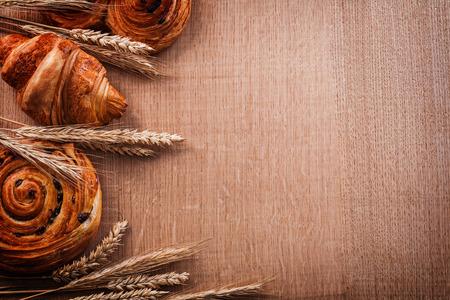 oaken: Composition of wheat ears bakery products on oaken wooden board Stock Photo