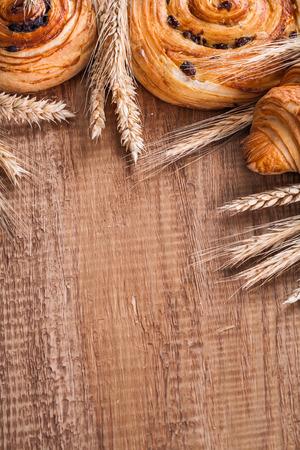 oaken: Composition of wheat ears raisin rolls croissant on oaken wooden