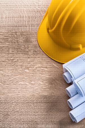 oaken: Construction helmet and blueprint rolls on wooden oaken board ma