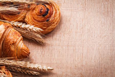 oaken: Golden wheat ears croissant bun with raisins on oaken wooden boa Stock Photo
