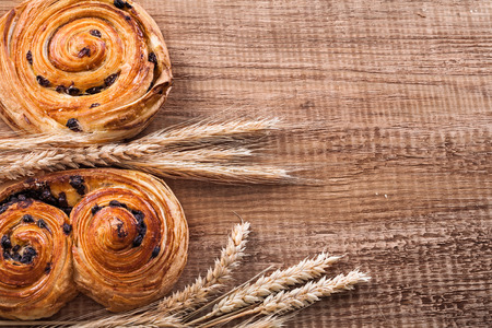 oaken: Golden wheat ears fresh-baked buns with raisins on oaken wooden
